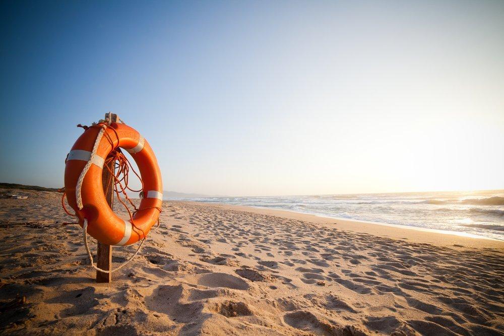 an orange life raft on a beach